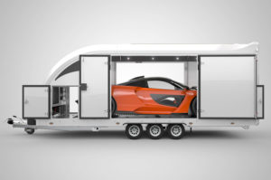 Enclosed trailer with side door open showing super car inside