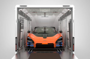 Enclosed trailer with back door open showing super car inside